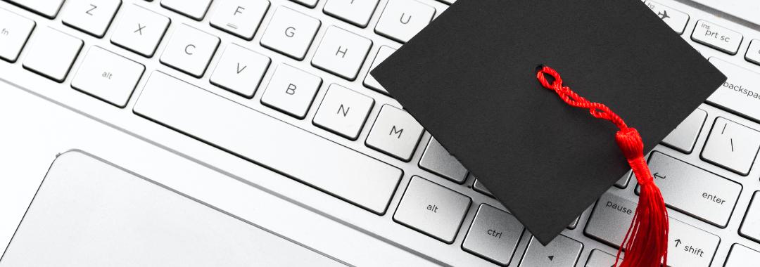 graduation cap on keyboard